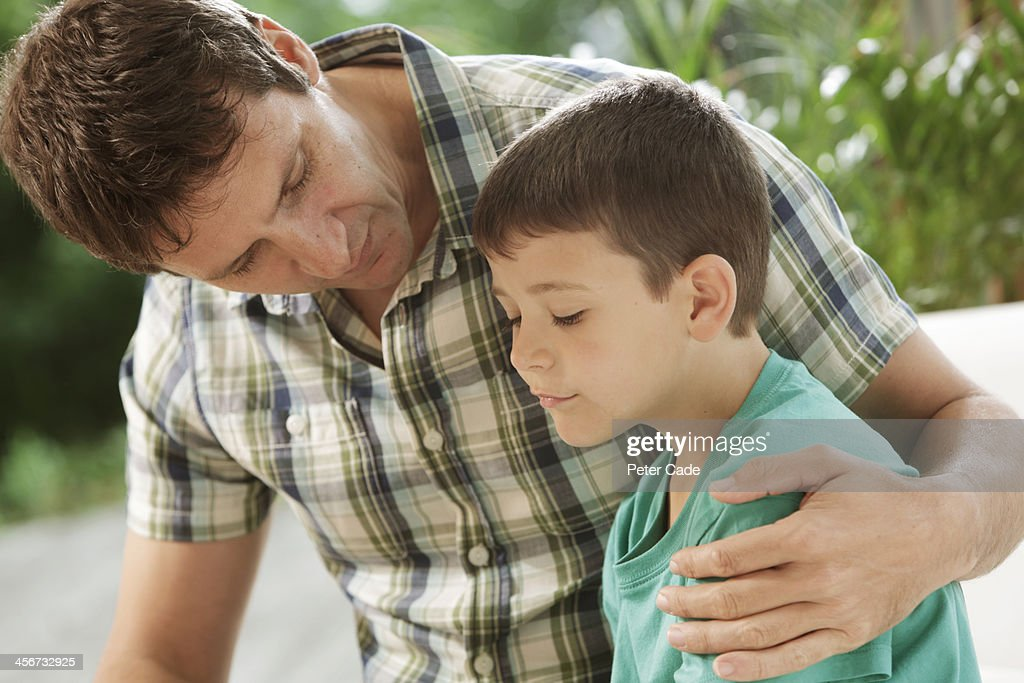 Father comforting son : Stock Photo