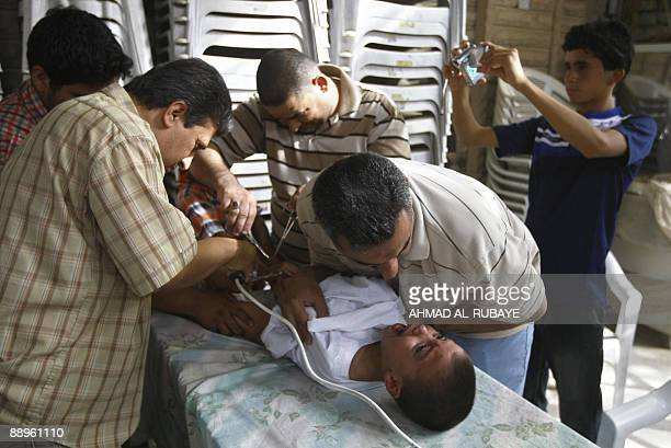 A father comforts his son as he under goes circumcision in the eastern Baghdad district of Sadr City on July 10 2009 Two hundred boys were...
