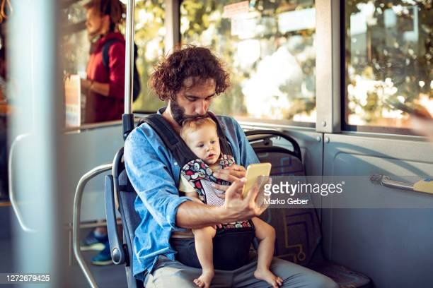 father commuting in a bus with his baby daughter - genderblend stock pictures, royalty-free photos & images