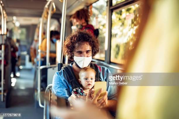 father commuting in a bus with his baby daughter - verkehrswesen stock-fotos und bilder