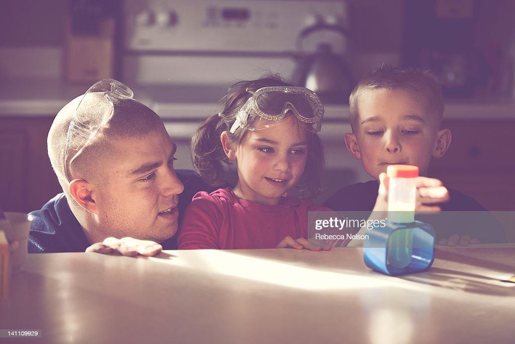 Father conducting science experiment with his kids : Stock Photo
