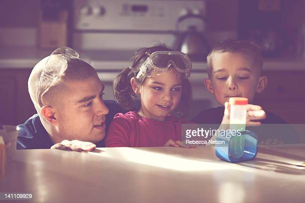father conducting science experiment with his kids - leanintogether stock pictures, royalty-free photos & images