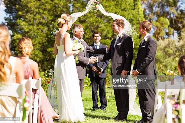 Father Congratulating Groom During Outdoor Wedding