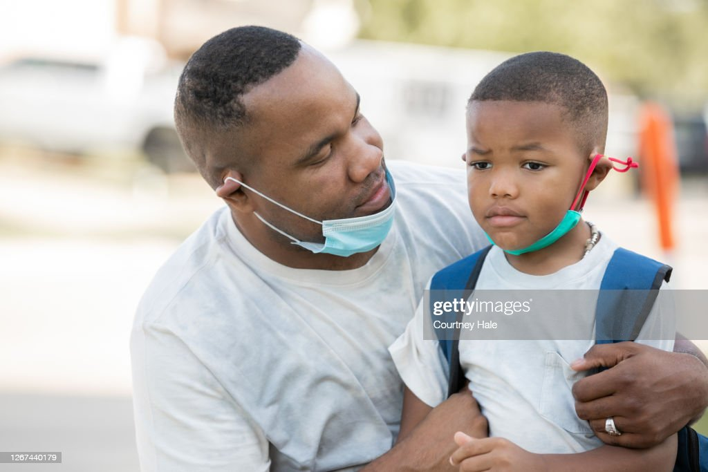 Father consoles anxious kindergartener while they wear masks as he's dropping him off for first day of school, : Stock Photo