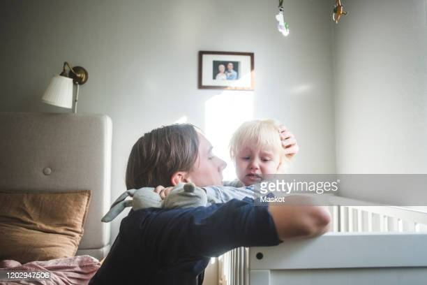 father consoling crying blond baby boy in crib with tender love at home - stay at home father stock pictures, royalty-free photos & images