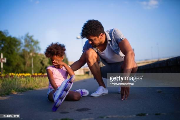 Père de consoler sa fille qui est tombé en patinage à roulettes