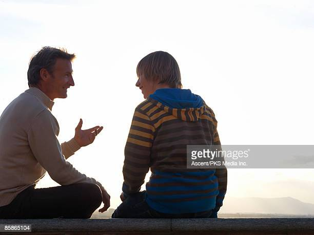 Father converses with son on top of wall, mtns