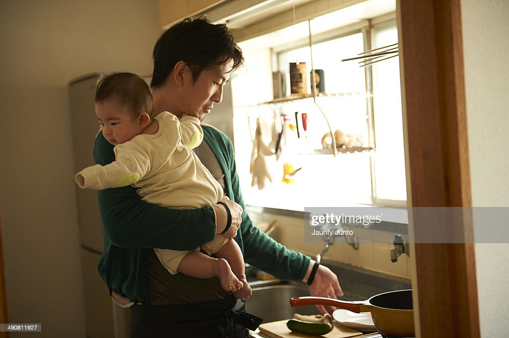 father cooking and holding his baby in the kitchen : Stock Photo