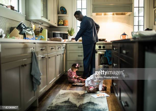 father cooking breakfast for daughters in kitchen - home interior stock pictures, royalty-free photos & images