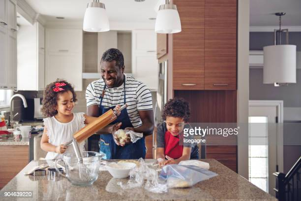 father cooking with kids - african american family home stock photos and pictures
