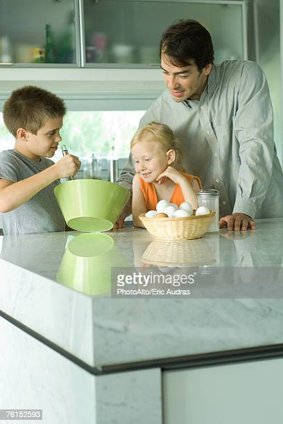 Father cooking with son and daughter