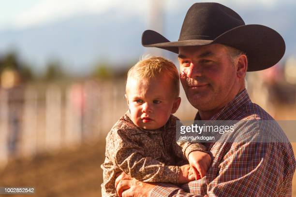 santaquin アメリカ合衆国ユタ slc ソルト レイク シティ近くのパドックでの赤ちゃんの息子と父のカウボーイ - ウエスタン映画 ストックフォトと画像