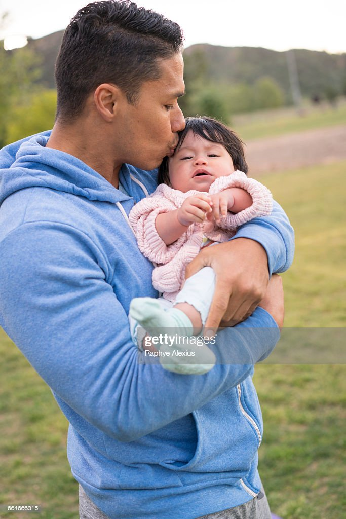 father cradling and kissing baby in park stock photo getty images