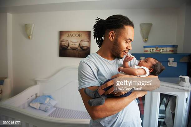 father cradling newborn baby in nursery - nursery bedroom stock pictures, royalty-free photos & images