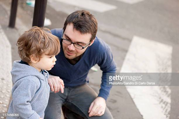 Father crouching beside toddler son, holding his hand