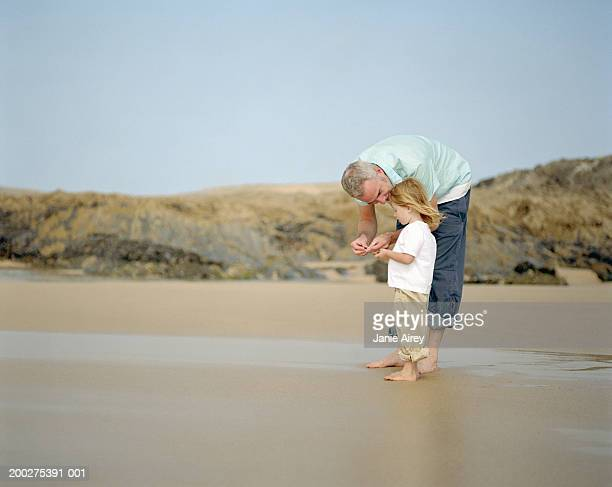 Father crouching by daughter (2-4) on beach