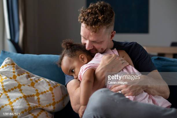 a father cuddles his sleepy daughter - toddler stock pictures, royalty-free photos & images