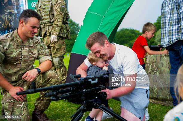 A father cuddles his son while looking at a GPMG during the event Stirling shows its support of the UK Armed Forces as part of the UK Armed Forces...