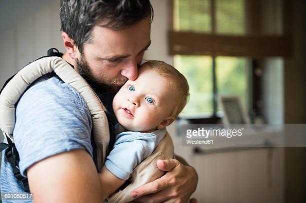 father cuddling with baby in baby carrier - padre amo de casa fotografías e imágenes de stock