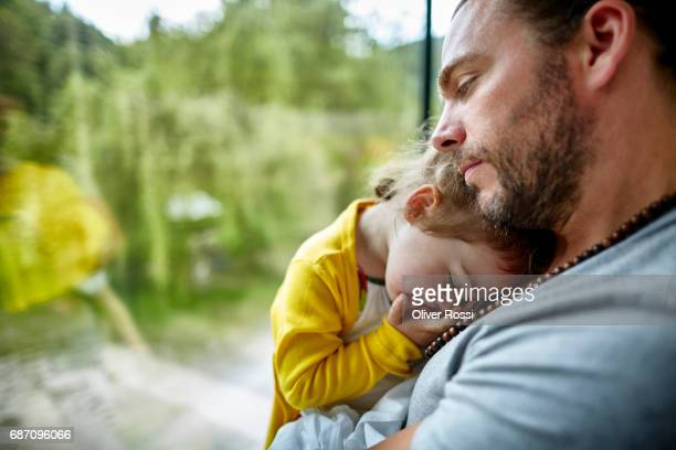 Father cuddling with little daughter at the window