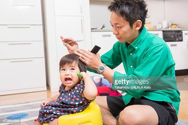 Father cutting baby's hair on floor