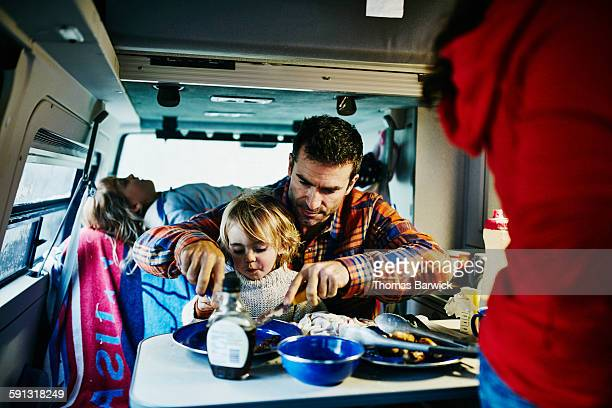 father cutting pancakes for son in camper van - leanintogether stock pictures, royalty-free photos & images