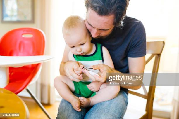 father cutting sons (12-17 months) fingernails - nail scissors stock pictures, royalty-free photos & images