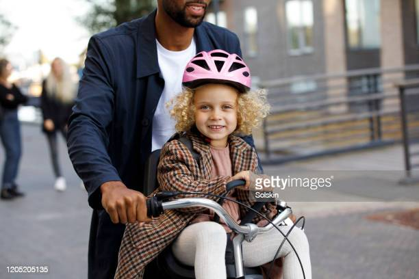 father cycling with daughter sitting in bicycle seat - copenhagen stock pictures, royalty-free photos & images