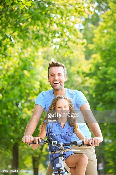 Father cycling with his daughter
