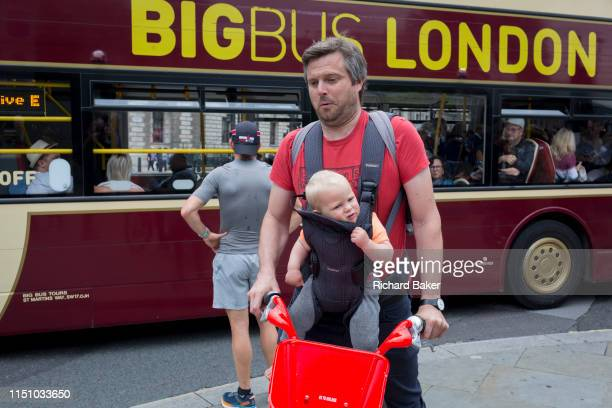 A father cyclist on a rental bike carries his child on a chest harness as a tour bus drives past in Parliament Square Westminster on 18th June 2019...