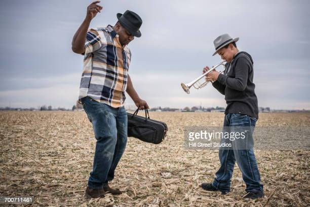 father dancing to son playing trumpet in field - tromba foto e immagini stock