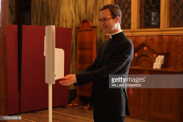 Father Daniel Humphreys uses a hand sanitizer station at Westminster Cathedral in London on June 15, 2020 after the church reopened for private...