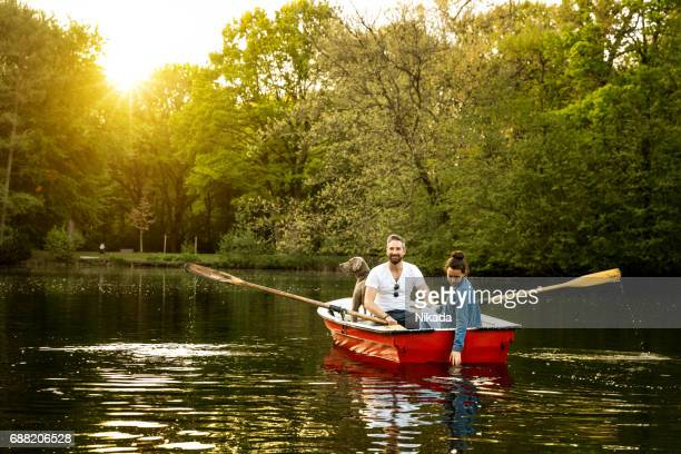 Father, daughter and dog in rowboat on lake