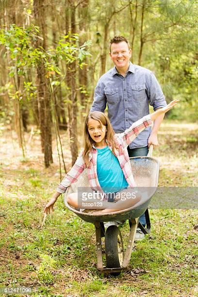 Père et fille nettoyage yard.   Famille sur le jardin extérieur.   Brouette de loisirs.