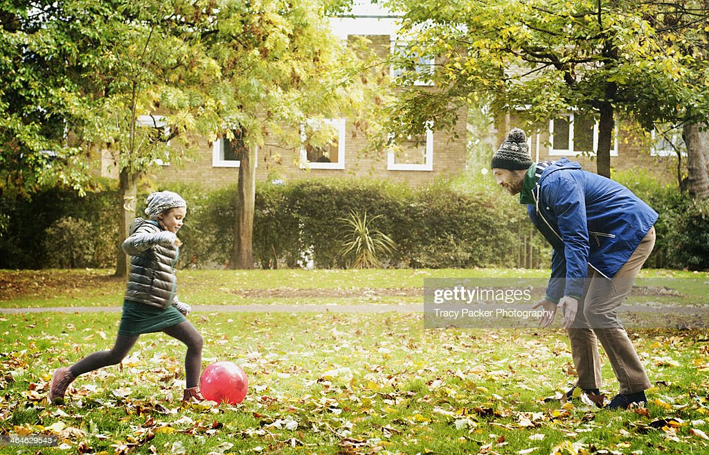 Father & daughter play football in a London park : Stock Photo