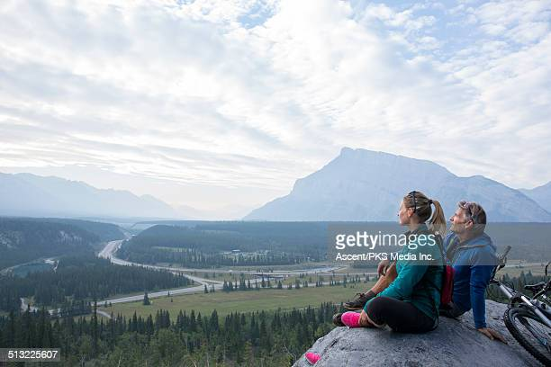 father & daughter relax with bikes on mtn ledge - leanintogether stock pictures, royalty-free photos & images