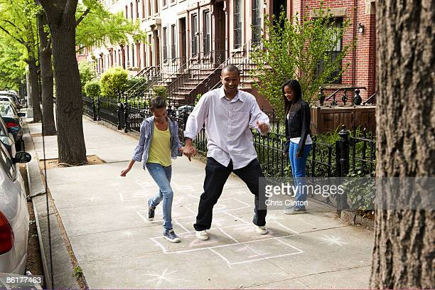 father & daughters playing hop-scotch - hopscotch stock pictures, royalty-free photos & images