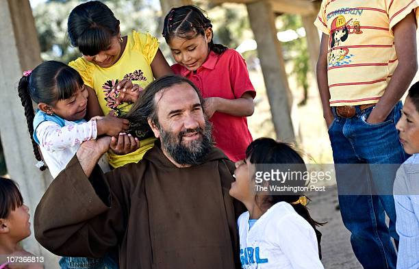 Father David Beaumont a Franciscan friar lets the Pima children braid his hair during a visit to their village in the Sierra Madre mountains of...