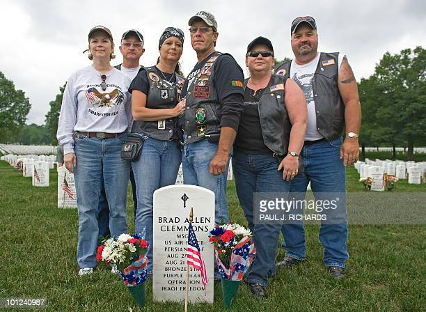 Father David Clemmons and unidentified friendS stand at the gravesite in Arlington National Cemetery of his son May 28 2010 US Air Force Master Sgt...