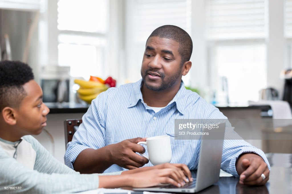 Father dictates life event for son's school project : Stock Photo