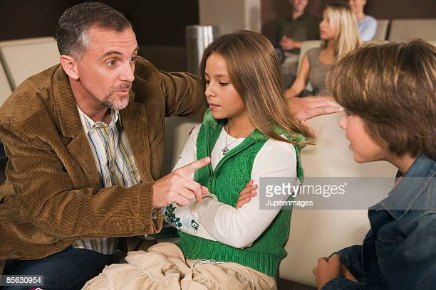 Father disciplining children on airplane