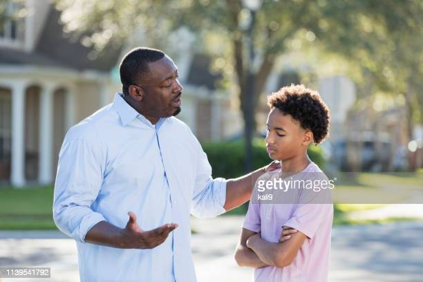 father disciplining or giving advice to teenage boy - sulking stock pictures, royalty-free photos & images
