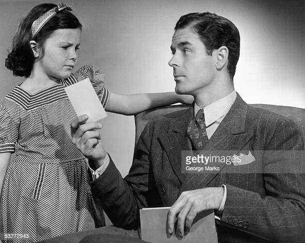 Father discussing poor report card w/daughter