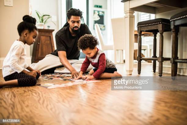 Father doing a puzzle with his children