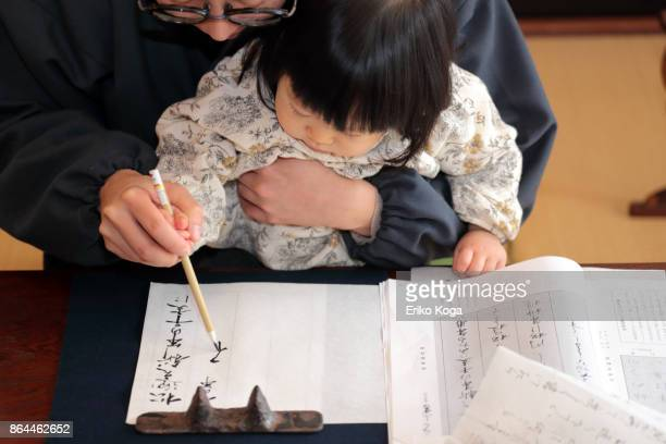 Father doing calligraphy with baby