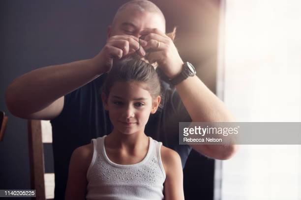 father doing his daughter's hair - role reversal stock photos and pictures