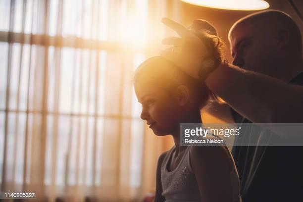 father doing his daughter's hair - pferdeschwanz stock-fotos und bilder