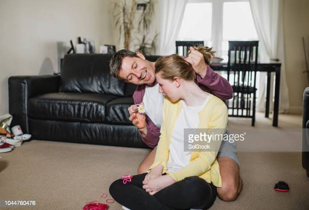 father doing his disbaled daughter's hair - als stock photos and pictures