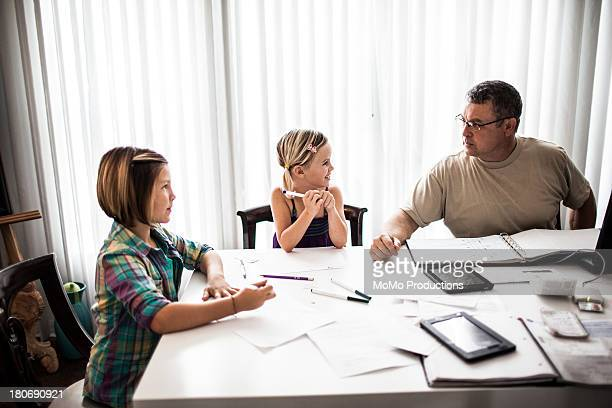 father doing homework with daughters - leanintogether stock pictures, royalty-free photos & images