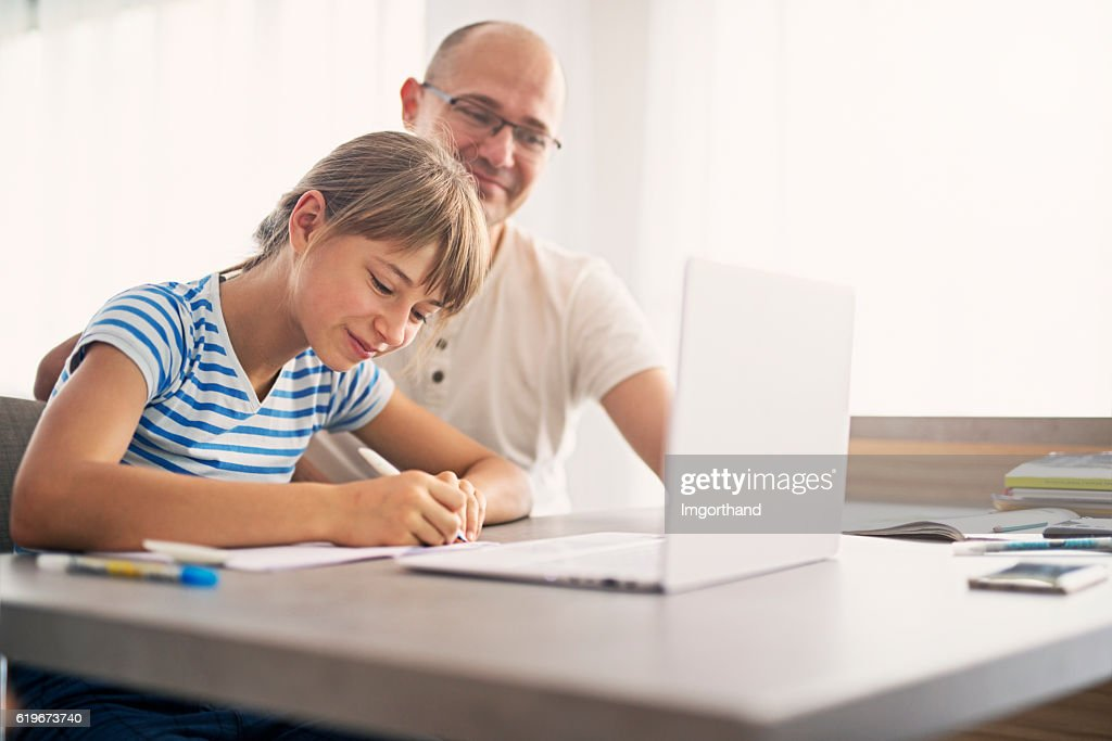 Father doing homework with his daughter : Stock Photo
